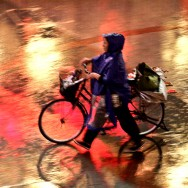 Lady in Rain Coat walking with her bike in the rain
