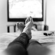 Legs on couch in front of the TV